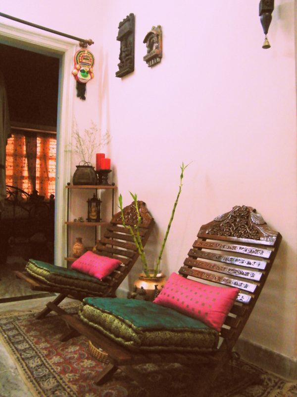 A kathakali mask overlooking Two low seating carved chairs with comfortable cushions.