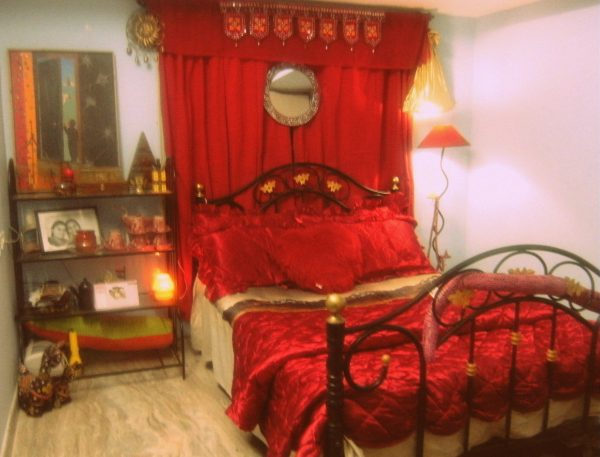 A bedroom filled with so much red. Red curtains, red pillows, red lamp and red blanket.