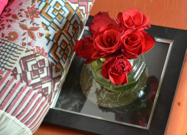 A bunch of red roses in a glass pickle jar