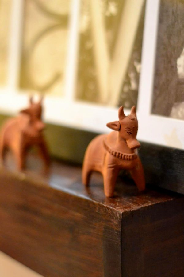 Two tiny terracotta cows one behind the other.