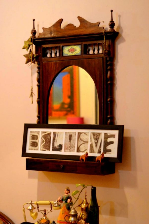 The colonial rosewood mirror with a lettering art frame on it.