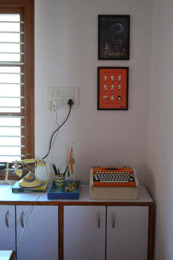 A painted white storage unit at the corner with a vintage typewriter.