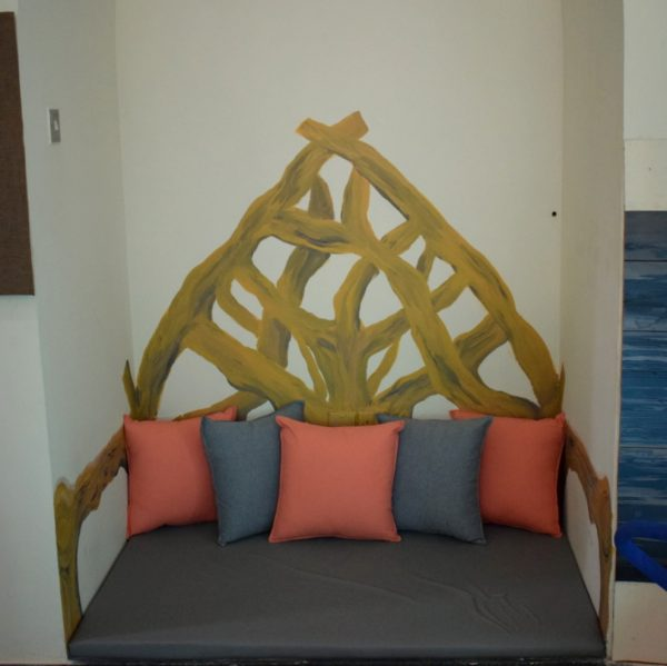 A niche in the wall is the perfect setting to draw a wooden throne mural and put some cozy cushions.