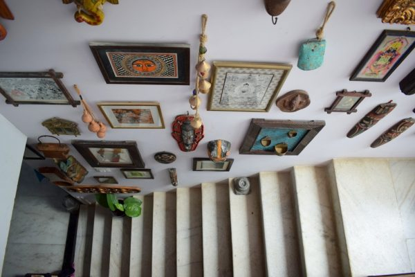 A gallery wall with art, masks and some odds and ends