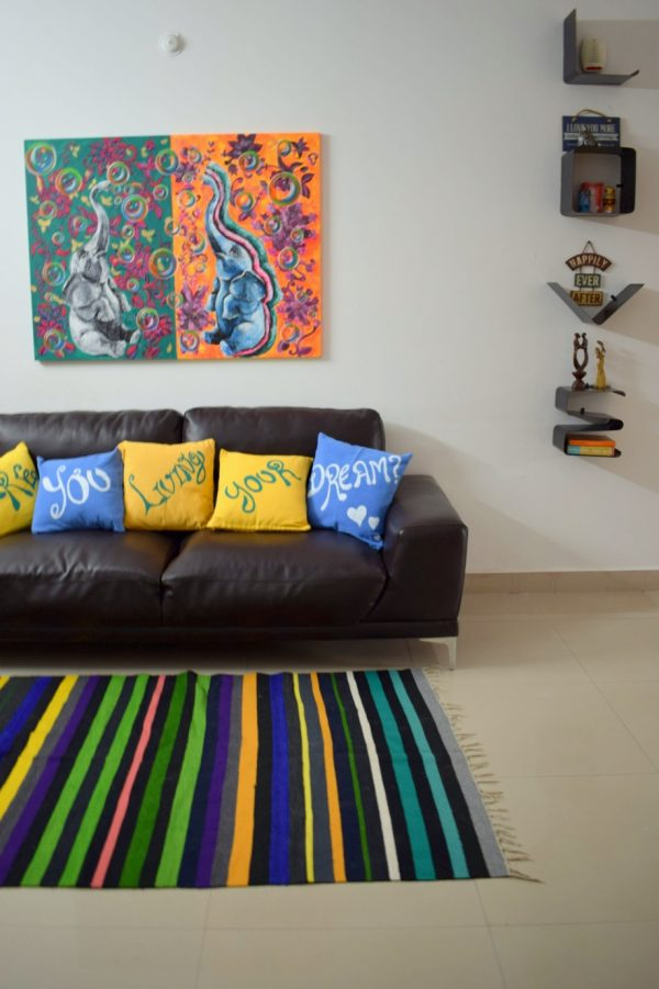 Striped rug with a gorgeous painting on the wall.