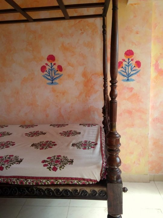 Antique Indian Day bed with vintage texure on the wall. The wall also has block printed motifs.