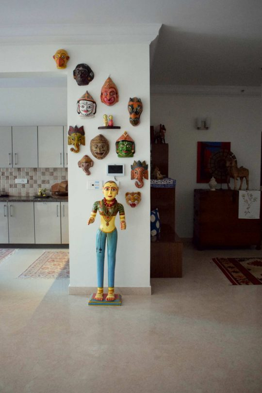 A wall full of masks and a four feet Gangaur doll greets you at the kitchen entrance.