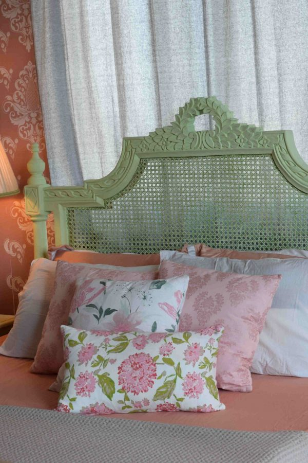 Pink floral cushions on a pastel green bed.