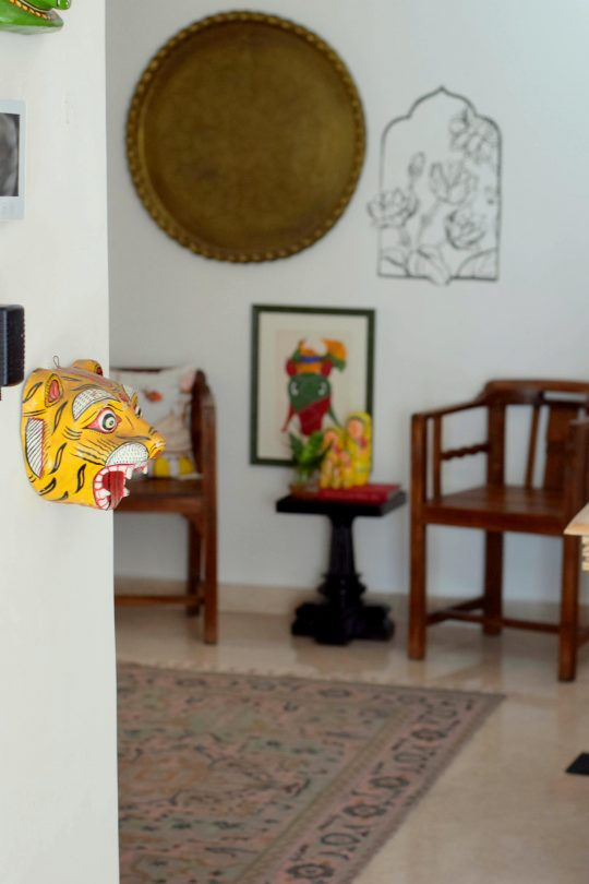 Two wooden chairs and the biryani plate in the background. The tiger masks looks on in the home of Preethi Prabhu.